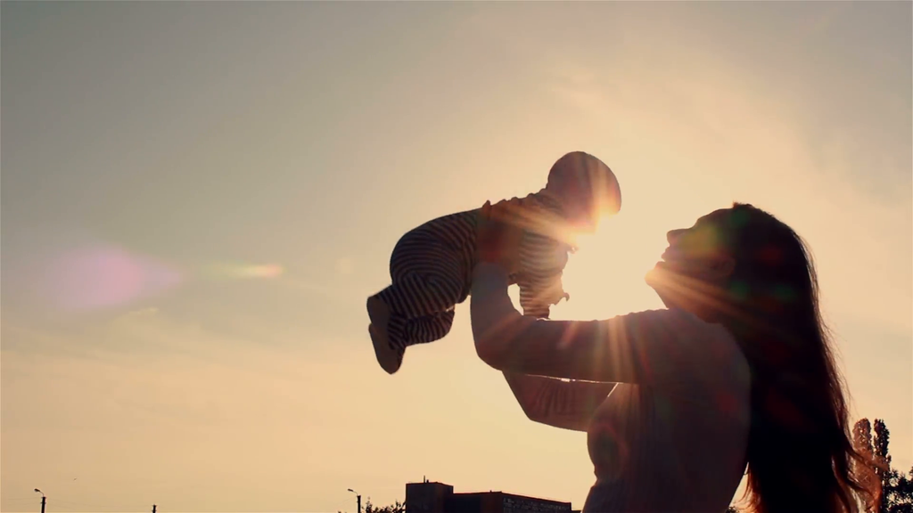 Mother raises child silhouette at sunset